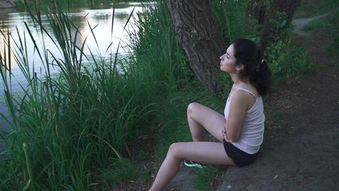 Sad girl on the river bank Footage