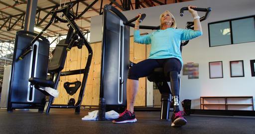 Senior woman doing exercise on chest press machine 4k Live Action