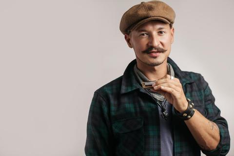 Studio portrait of caucasian moustached man on cap playing harmonica Fotografía