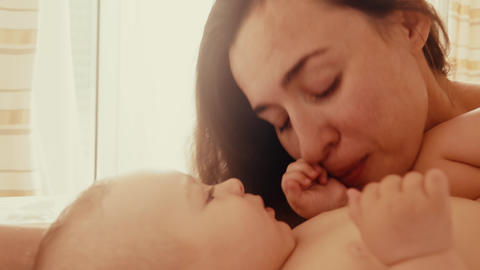 Happy mom playing with her baby in bed Footage