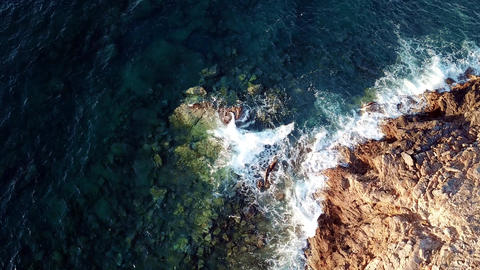 Aerial top down view of crystal clear waves at a rocky coast with clear blue Live Action