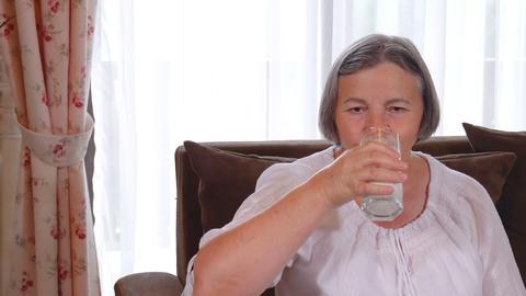 Healthy senior lady drinking a glass of fresh milk Footage