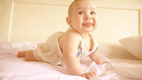Funny baby learning to crawl in bed フォト
