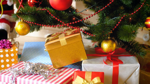Lots of colorful presents and gift boxes lying under beautiful Chrsitmas tree in Footage