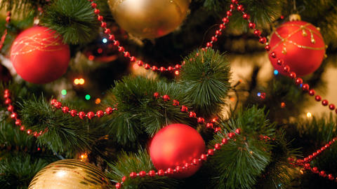 CLoseup 4k video of colorful lights and baubles hanging on CHristmas tree at Footage