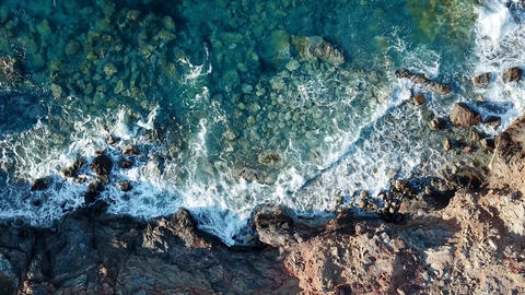 Aerial top down view of crystal clear waves at a rocky coast with clear blue Footage