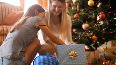 4k footage of happy family taking cat out of Christmas gift box. Pet as gift for Live Action