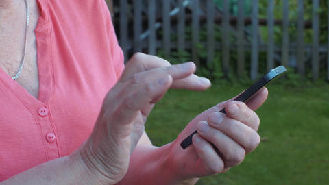Hands of senior woman touching screen mobile phone in summer garden Footage