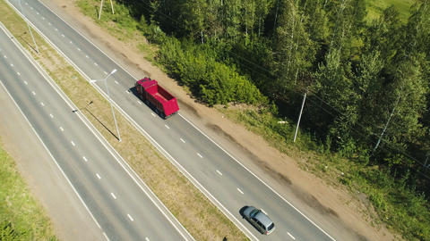 red lorry moves along highway to distant city on horizon Footage