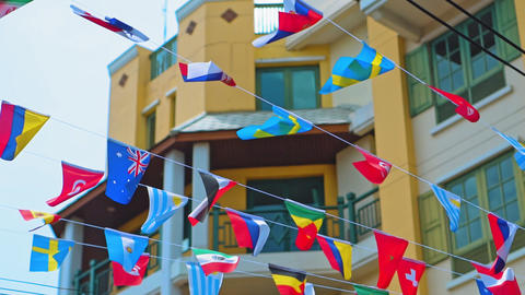 garland of flags on a city street GIF