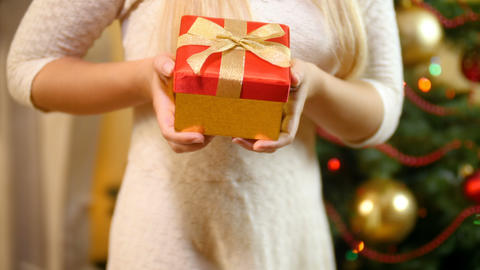 Closeup 4k video of young woman holding Christmas gift and showing it in camera Footage