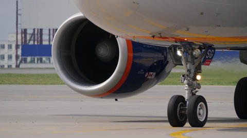 Landing gear and engine of jet airliner. Fuselage reflects taxiway marking Footage