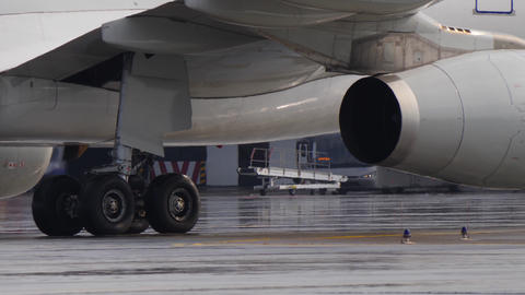 Landing gear and engine of jetliner taxiing on wet airport ramp. Sunlight spots Footage