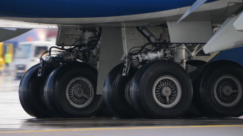 Wheels of aircraft undercarriage. Close up of taxiing airplane landing gear Footage