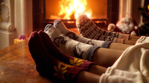 Closeup 4k video of family wearing woolen socks lying under blanket and warming Live Action