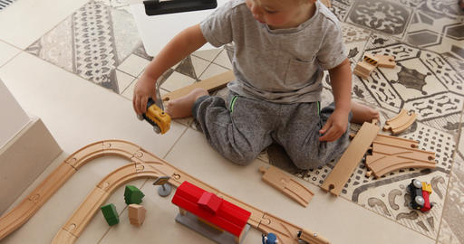 Two years old boy plays with wooden railroad Footage