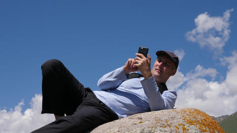 Man using phone while lying on stone in mountains ライブ動画