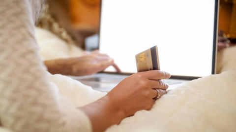 Closeup image of young woman lying in bed and doing online shopping Fotografía