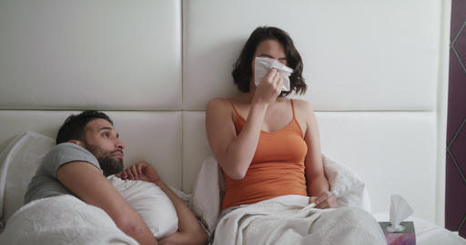 Young Woman Sneezing For Cold In Bed With Man Footage