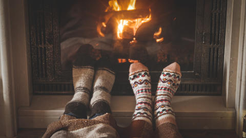 Toned closeup image of man and woman wearing woolen socks and lying by the Fotografía