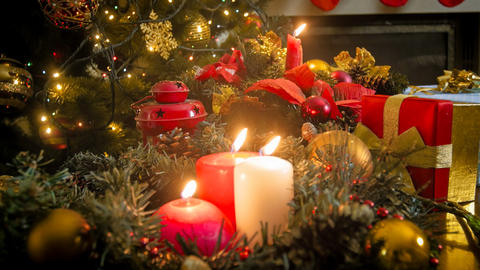 Closeup image of three burning candles against glowing colorful Christmas lights Photo