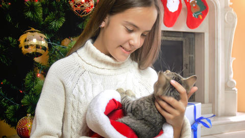 Portrait of beautiful teenage girl in woolen swweater hugging kitten under Fotografía