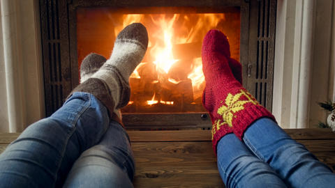 Closeup image of romantic couple and jeans and woolen socks warming by the Photo