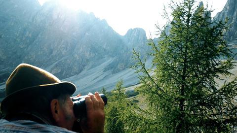 elderly man looks through the binoculars towards the mountains GIF