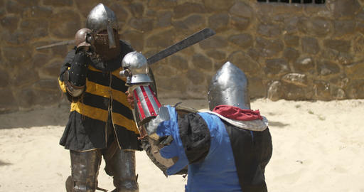 Medieval tournament. Two strong warrior knights fighting at arena GIF