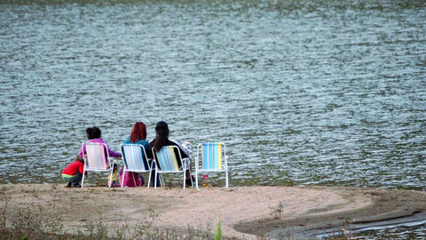 family resting on the shores of the lake sitting in a chairs Footage