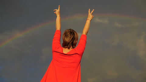 Woman that shows her thumbs and sign peace into the sky during rainbow Live Action