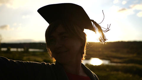 Silhouette of middle aged woman that standing at sunset in student hat GIF