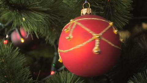 Closeup slow motion footage of beautiful red bauble spinning on decorated Footage