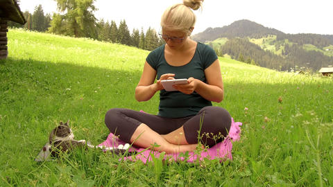 blonde girl chatting with tablet on a green lawn Live Action