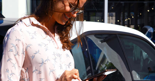 Woman using digital tablet while charging electric car 4k Live Action