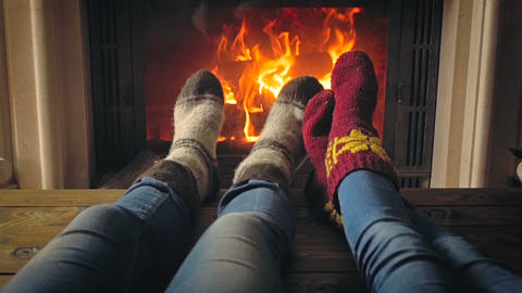 Toned footage of two people in woolen knitted socks warmning at fireplace Live Action