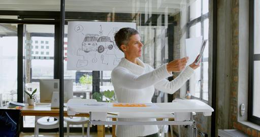 Car designer checking car sketch design in office 4k Live Action