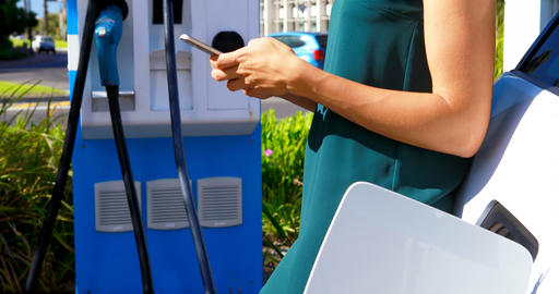 Woman using mobile phone while charging electric car 4k Live Action