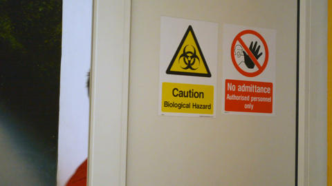 Zoom in on Caution Biological Hazard and No Admittance warning danger signs on Footage