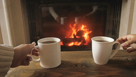 Slow motion video of family relaxing by the fireplace and taking mugs with hot Live Action