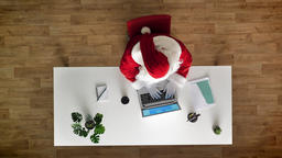Santa Claus working at office on laptop, typing, drinking cofee, aerial view Footage