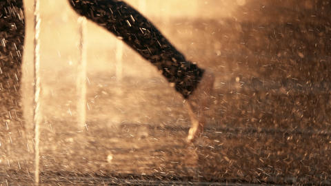 Slow motion shot of defocused barefooted person running in a fountain on a Footage