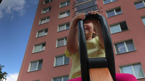 Childhood in city: smiling toddler on spinning ride between high-rise blocks Footage