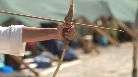 A hand pulls a string on a bow Aim and shot Slow motion video Live Action
