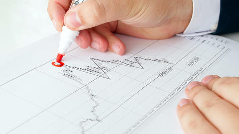 Closeup 4k footage of financial writing with red marker on financial diagram Footage