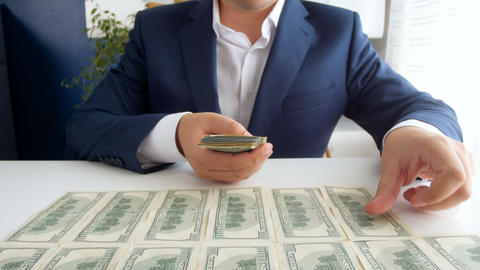 4k footage of successful businessman laying and counting big stack of US dollars Footage