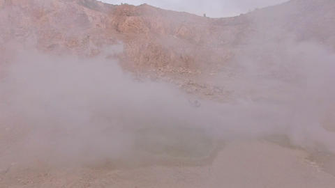A young emotional woman stands in smoke against a background of mountains near a GIF