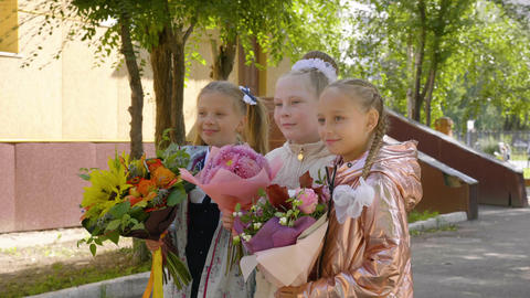 Three school girls with flowers posing for camera. Back to school concept ライブ動画