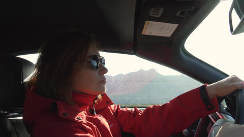 Young woman is driving a car on a sunny day Footage