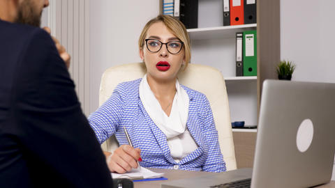 Human resource woman taking notes and talking with a canditate for the new job Footage